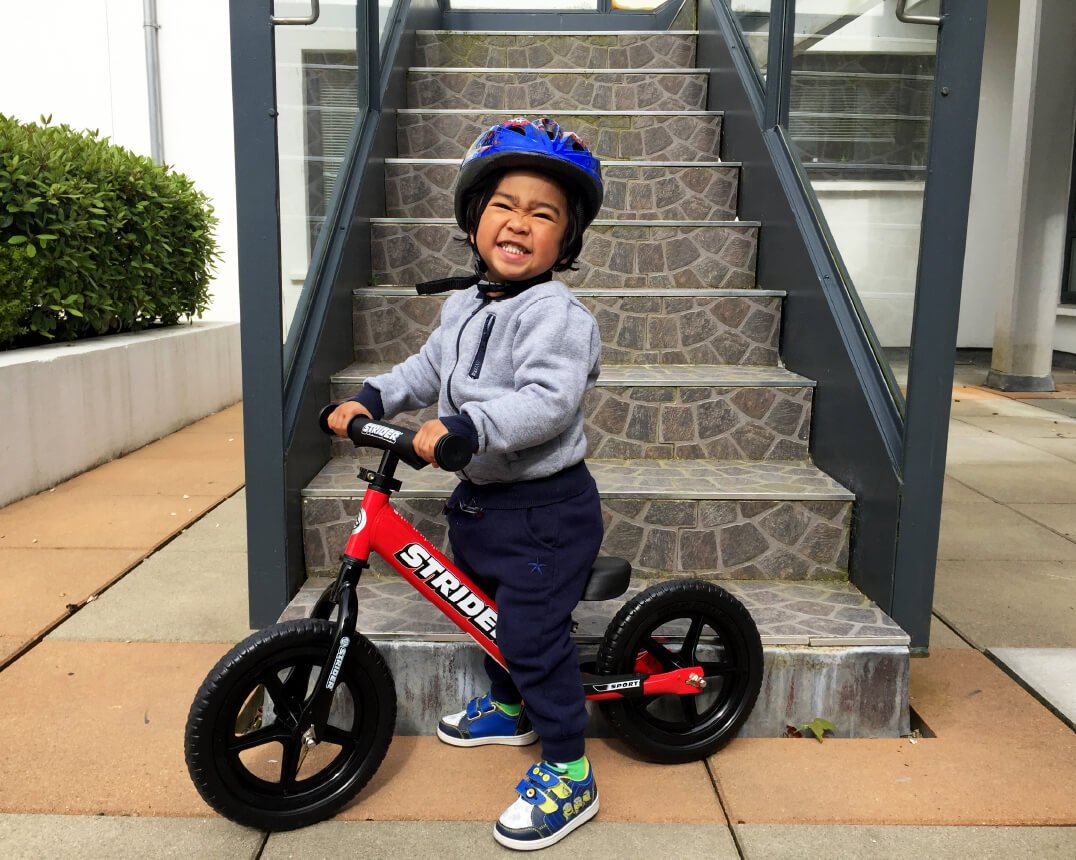 Child on red Strider 12 Sport Balance Bike